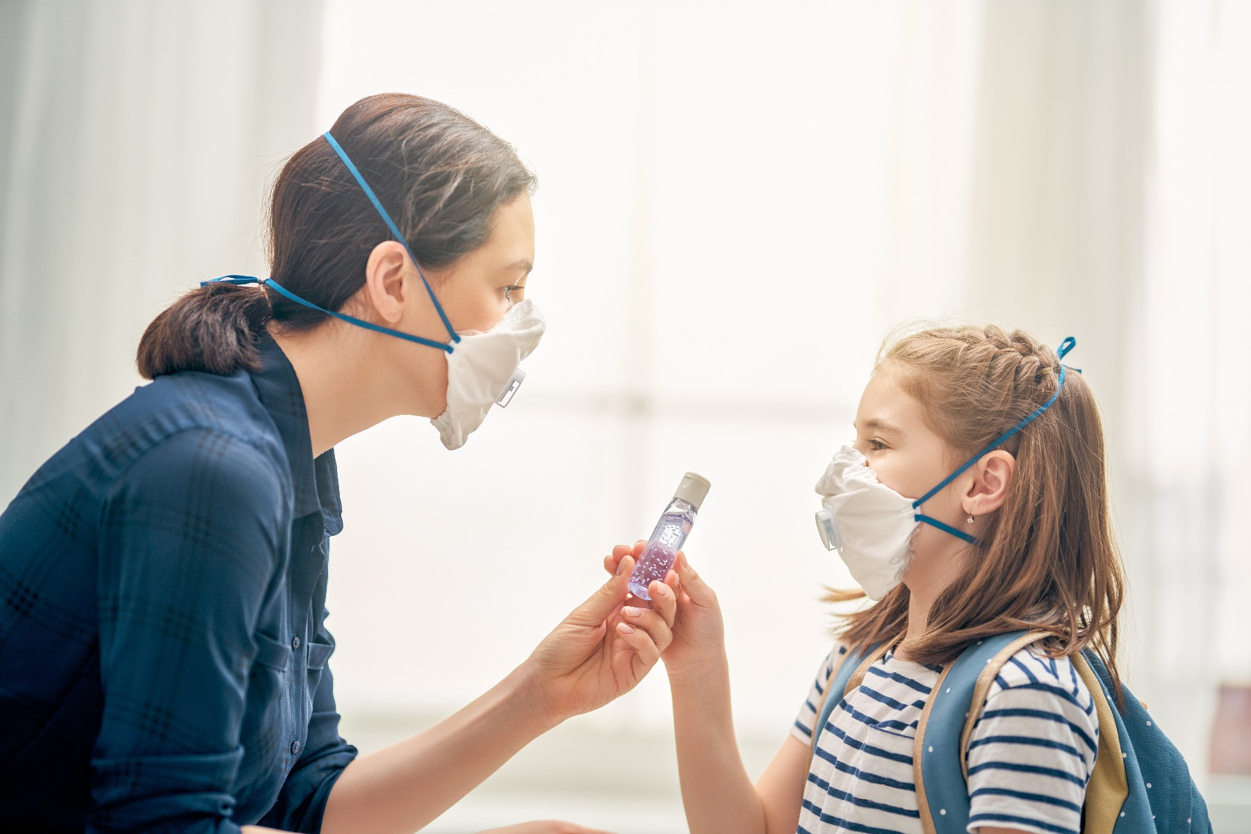 Parent giving child hand sanitizer